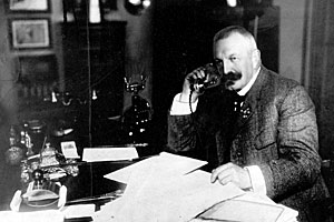 Black and white picture of Amandus Schibsted sitting at his desk talking on the phone